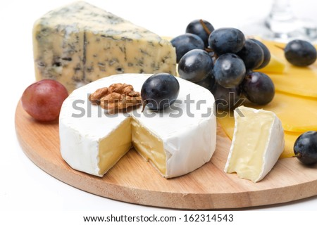 Assorted cheeses and grapes on a wooden board, isolated on white - stock photo