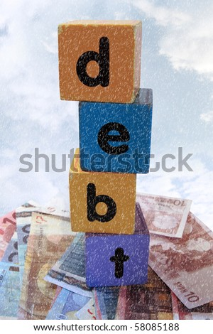 assorted childrens toy letter building blocks against a stormy background on money that spell debt - stock photo