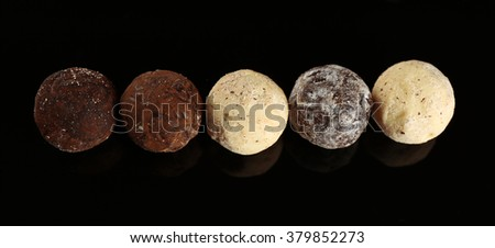 Assorted chocolate candies on black background - stock photo