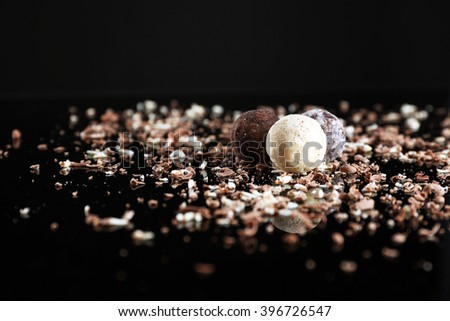 Assorted chocolate candies with flakes on black background - stock photo