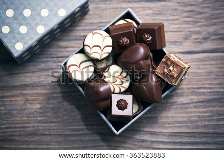 Assorted chocolate pralines on a wooden background. Romantic style - stock photo