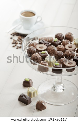 assorted chocolates confectionery on tray with cup of coffee - stock photo