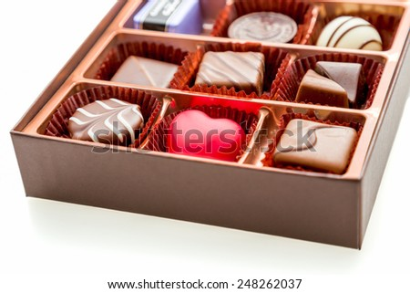 Assorted chocolates in brown box, with red heart chocolate - stock photo
