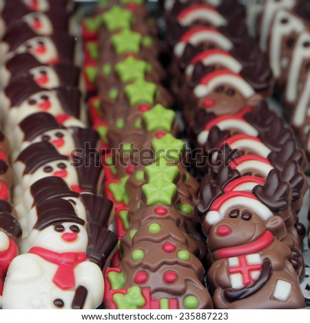 assorted christmas chocolates in shape of snowman,christmas tree and reindeer in italian pastry shop window  - stock photo