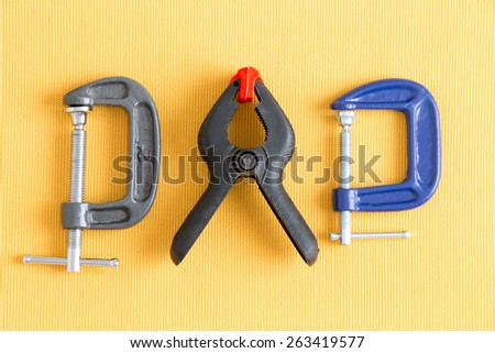 Assorted clamps from Dad's tool kit with adjustable grey and blue G-clamps and a spring loaded plastic A-clamp arranged in a line on a yellow background in a DIY concept - stock photo