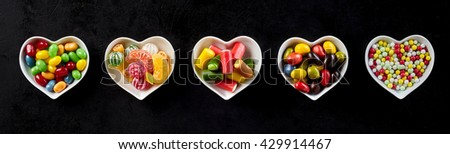 Assorted colorful candy banner in heart-shaped dishes over black with five bowls in a line filled with different sweets for Valentines or an anniversary celebration - stock photo