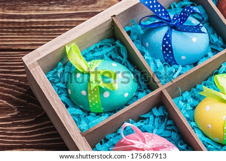 assorted colorful painted easter eggs in a wooden box - stock photo