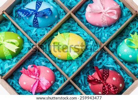 assorted colorful painted easter eggs in a wooden box. Focus on bows - stock photo