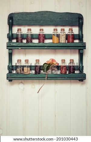 Assorted colorful spices in bottles on a green rack on wooden background  - stock photo