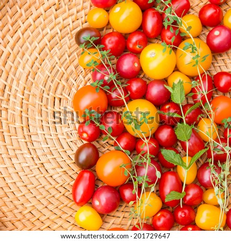 Assorted colorful tomatoes and herbs from the garden. - stock photo