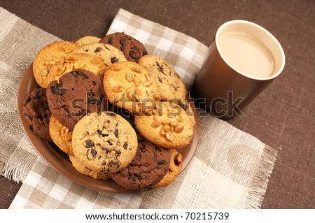 Assorted cookies in brown plate and brown mug of coffee on linen napkins. - stock photo