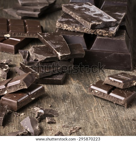 Assorted dark chocolate bars and chopped chocolate on vintage wooden background. - stock photo