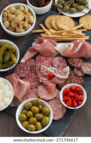 Assorted deli meat snacks, sausages and pickles on blackboard, vertical, top view - stock photo