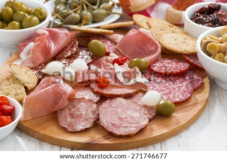 Assorted deli meat snacks, sausages and pickles on board, close-up - stock photo