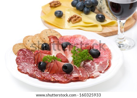 assorted deli meats, a plate of cheese and a glass of wine, isolated on white - stock photo