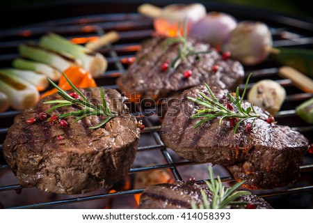Assorted delicious beef steaks with vegetable on a barbecue grill. - stock photo