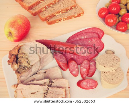 Assorted delicious low fat meats, salamis and sausages on ceramic cutting board. Image done in retro style with vintage effect - stock photo