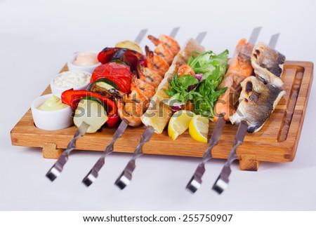 Assorted fish kebabs, king big shrimp wood - stock photo