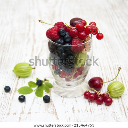 Assorted fresh berries on a wooden  background - stock photo