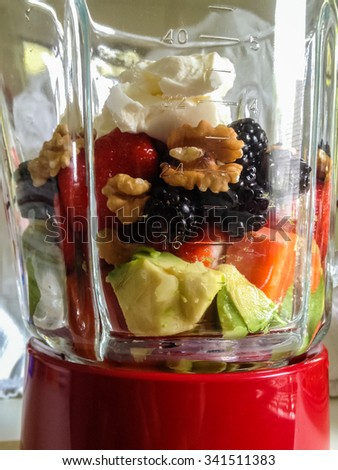 Assorted fresh fruits for healthy low carb smoothie in blender.  Avocados, blackberries, walnuts, strawberries, melon, cream, apples in mixer for diet cocktail - stock photo