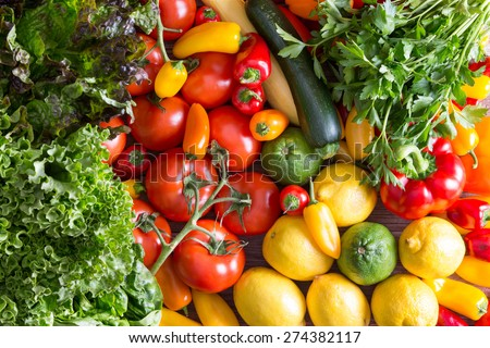 Assorted Fresh Healthy Organic Vegetables - Lettuces, Tomatoes, Peppers, Lemons, Limes, Italian Parsley, Zucchini - on Top of Wooden Table in High Angle View - stock photo