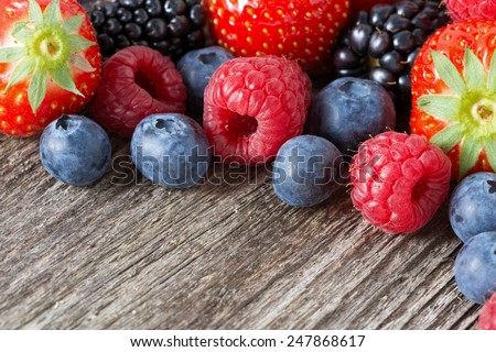 assorted fresh juicy berries on wooden background, horizontal, close-up - stock photo