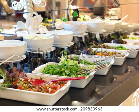 Assorted fresh salads displayed on a buffet in individual containers at a catered event or celebration, receding perspective - stock photo