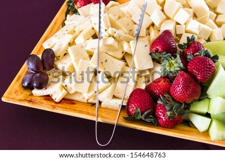 Assorted fruits and cheese hors d'oeuvres on decorated serving platter - stock photo