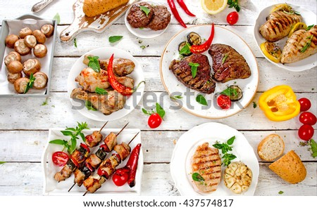 Assorted grilled meats and vegetables on a white wooden table. Healthy eating. View from above - stock photo