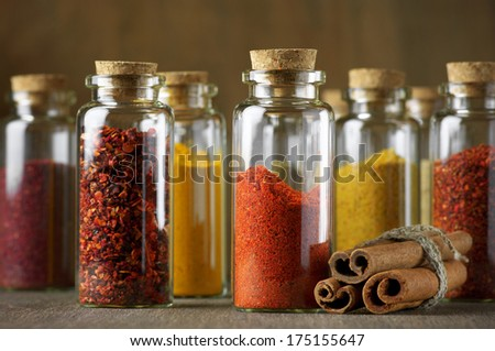 Assorted ground spices in bottles and cinnamon sticks on wood. - stock photo
