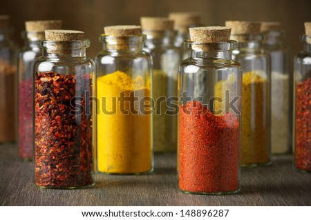 Assorted ground spices in bottles on wood. - stock photo