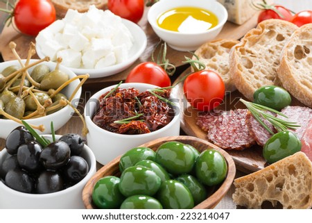 assorted Italian antipasti - olives, salami, pickles and bread, close-up - stock photo