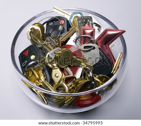Assorted keys in glass bowl - stock photo