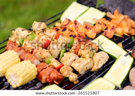 Assorted meat and vegetables on barbecue grill cooked for summer family dinner - stock photo
