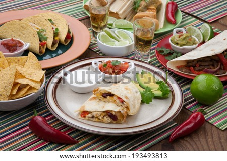 Assorted Mexican dishes, with chicken quesadilla as the main subject.  - stock photo