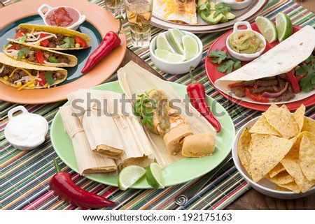 Assorted Mexican dishes, with chicken tamales with green salsa as the main subject.  - stock photo