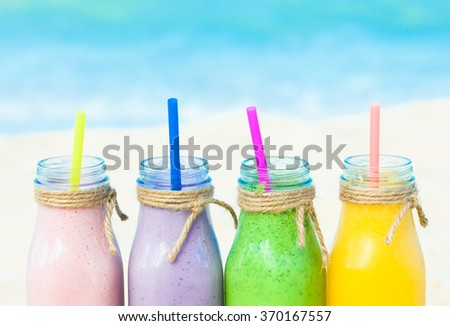 Assorted milk shakes on the beach.  - stock photo