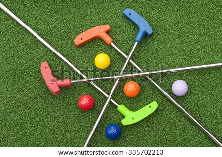 Assorted miniature golf putters and balls askew on synthetic grass - stock photo