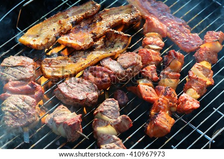 Assorted mixed grill on wooden skewers from chicken meat, lamb and pork, marinated spareribs, sausages and various vegetables roasting on barbecue grid cooked for summer family dinner - stock photo