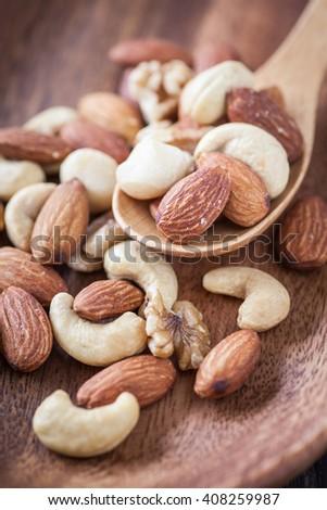 Assorted mixed nuts , Almond , Cashews nuts , macadamia , walnut in wood spoon - stock photo