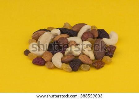 Assorted mixed nuts-almond, hazelnut, cashew, brazil nut on yellow tablecloth. - stock photo