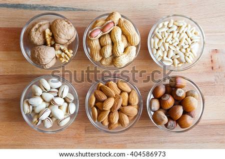 Assorted nuts in bowls: walnut, pistachios, almond, peanut, hazelnut, pine nuts - stock photo