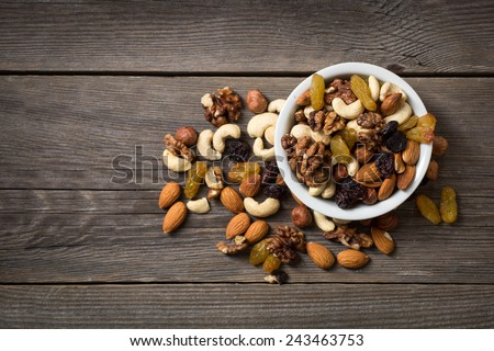 Assorted nuts in white bowl on wooden surface. - stock photo