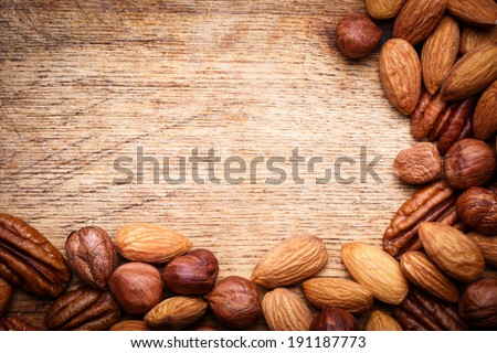 Assorted nuts. Nuts mix. Heap of nuts. Nuts seeds. Mixed nuts. Nuts on wooden texture background. Assorted nuts including, almonds, pecan, hazelnut. Nuts set. Pile of nuts. Natural food. Healthy food. - stock photo