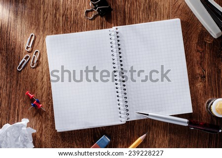 Assorted Office Supplies, Emphasizing Open Spiral Notebook with Copy Space for Texts, on Top of Wooden Table. - stock photo