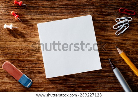 Assorted Office Supplies on Wooden Table, Emphasizing White Blank Notepad at the Center with Copy Space for Texts. - stock photo