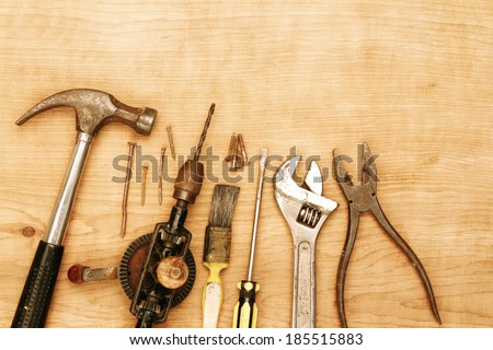 Assorted old work tools on wood - stock photo