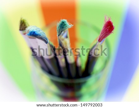 Assorted painting brushes in a glass cup. - stock photo
