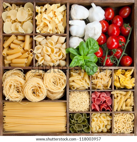 Assorted pastas in wooden box with cooking ingredients - stock photo