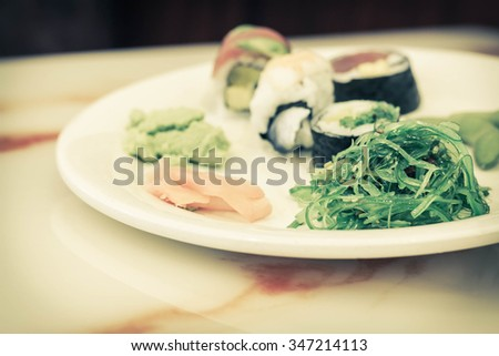Assorted plate of Japanese sushi demonstrating variety including edamame and seaweed salad - stock photo